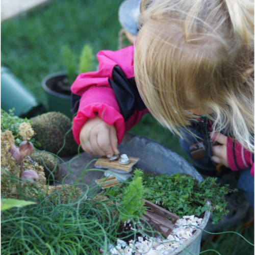 little girl playing with fairy garden