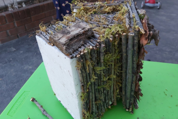 tiny log cabin style fairy house made from twigs