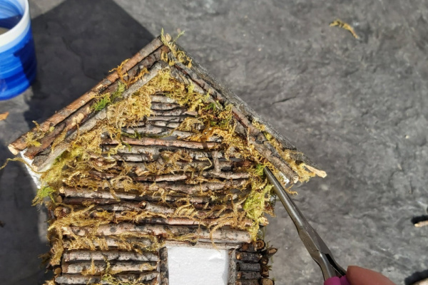 adding moss to fill the gaps on the diy twig fairy house