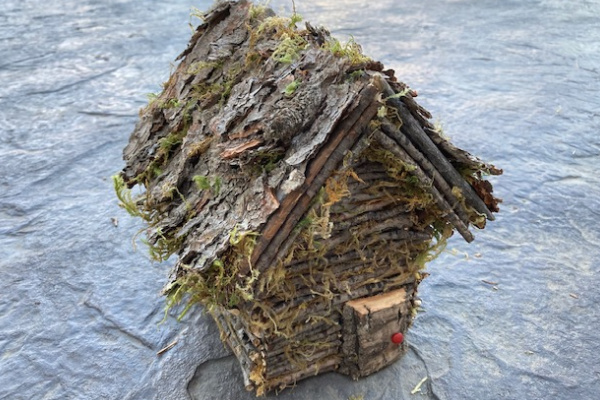 Log cabin fairy house made from twigs and bark