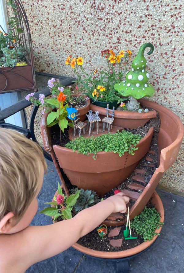child playing with broken pot fairy garden