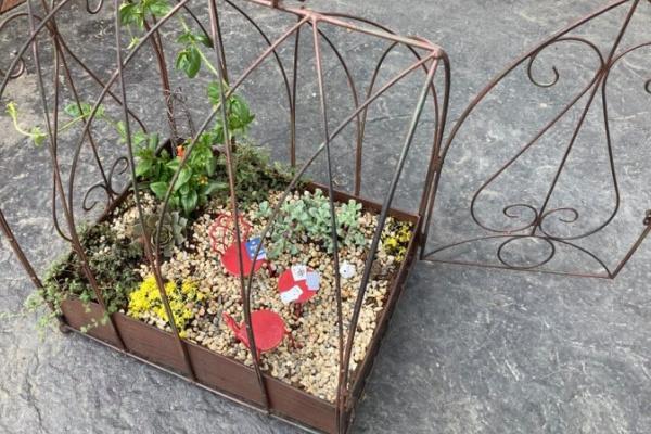 bird cage fairy garden with dollar store rocks in bottom